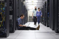 Man Sitting in Data Center with Notebook