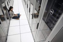 Woman Sitting in Data Center with Notebook